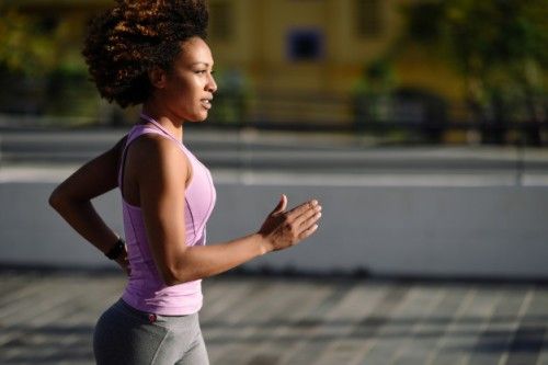 black-woman-afro-hairstyle-running-outdoors-in-urban-road_1139-1308